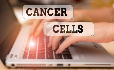 Writing note showing Cancer Cells. Business concept for forming solid tumors or flooding the blood with abnormal cells woman with laptop smartphone and office supplies technology