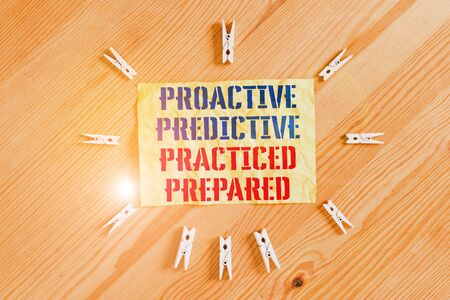 Writing note showing Proactive Predictive Practiced Prepared. Business concept for Preparation Strategies Management Colored clothespin papers empty reminder wooden floor background office