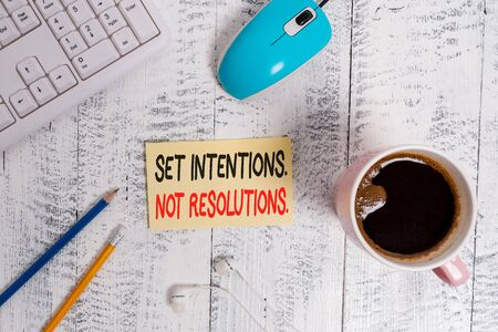 Conceptual hand writing showing Set Intentions Not Resolutions. Concept meaning Positive choices for new start achieve goals Technological devices colored reminder paper office supplies
