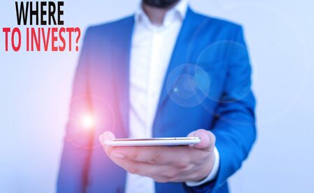 Word writing text Where To Invest Question. Business photo showcasing asking about where put money into financial schemes or shares Business concept with man holding mobile phone with touch screen Stok Fotoğraf