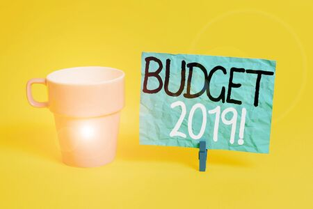 Handwriting text Budget 2019. Conceptual photo estimate of income and expenditure for current year Cup empty paper blue clothespin rectangle shaped reminder yellow office