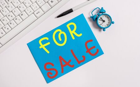 Writing note showing For Sale. Business concept for putting property house vehicle available to be bought by others Flat lay above empty note paper on the pc keyboard pencils and clock