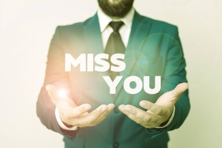 Text sign showing Miss You. Business photo showcasing Longing for an important demonstrating in your life for a period of time Man with opened hands in fron of the table. Mobile phone and notes on the table