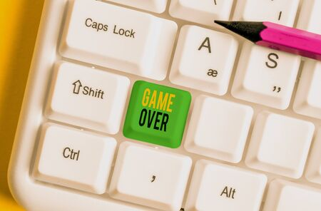 Word writing text Game Over. Business photo showcasing A situation in a particular sport that reach his finals or ending White pc keyboard with empty note paper above white background key copy space