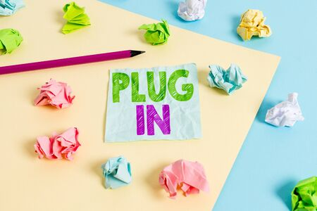 Handwriting text Plug In. Conceptual photo putting device into electricity to turn it on Power it Connecting Colored crumpled papers empty reminder blue yellow background clothespin Imagens