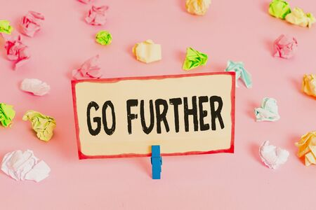 Conceptual hand writing showing Go Further. Concept meaning To move to a greater distance or overcome your limitations Colored crumpled papers empty reminder pink floor clothespin