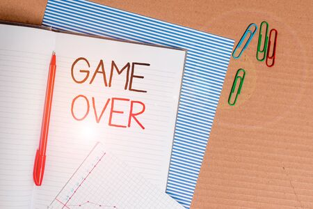 Writing note showing Game Over. Business concept for A situation in a particular sport that reach his finals or ending Striped paperboard notebook cardboard office study supplies chart paper