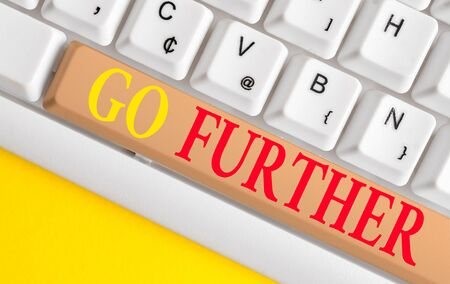 Conceptual hand writing showing Go Further. Concept meaning To move to a greater distance or overcome your limitations White pc keyboard with note paper above the white background