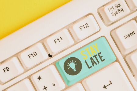 Conceptual hand writing showing Stay Late. Concept meaning A routine in which a demonstrating goes to somewhere out of time White pc keyboard with note paper above the white background Stock Photo