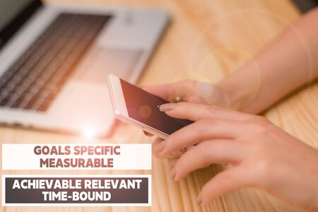 Handwriting text writing Goals Specif Measureable AC. Conceptual photo Goals Specific Measurable Achievable Relevant Time Bound woman laptop computer smartphone mug office supplies technological devices