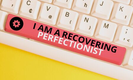 Conceptual hand writing showing I Am A Recovering Perfectionist. Concept meaning Obsessive compulsive disorder recovery White pc keyboard with note paper above the white background