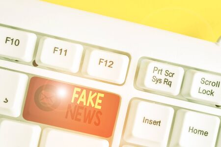 Text sign showing Fake News. Business photo text Giving information to showing that is not true by the media White pc keyboard with empty note paper above white background key copy space