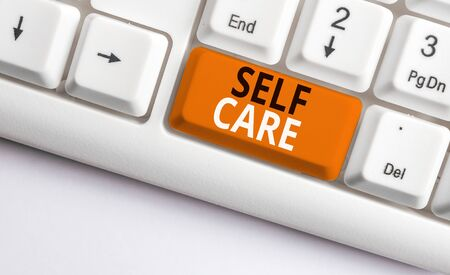 Writing note showing Self Care. Business concept for Give comfort to your own body without professional consultant White pc keyboard with note paper above the white background