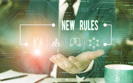 Text sign showing New Rules. Business photo showcasing A state of changing an iplemented policy for better upgrade Male human wear formal work suit presenting presentation using smart device Stock Photo