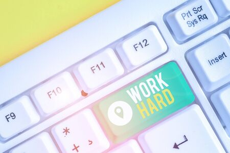 Text sign showing Work Hard. Business photo text Laboring that puts effort into doing and completing tasks White pc keyboard with empty note paper above white background key copy space Stock Photo