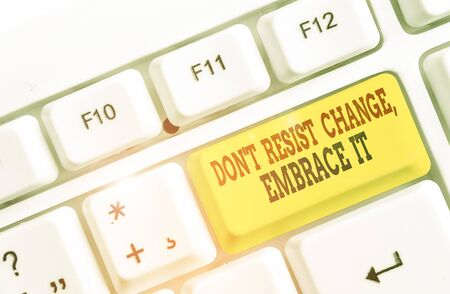 Conceptual hand writing showing Don T Resist Change Embrace It. Concept meaning Be open to changes try new things positive White pc keyboard with note paper above the white background