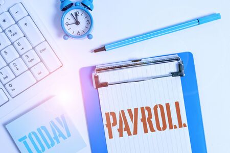 Writing note showing Payroll. Business concept for Amount of wages and salaries paid by a company to its employees Flat lay above table with clock pc keyboard and copy space note paper