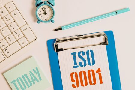 Writing note showing Iso 9001. Business concept for designed help organizations to ensure meet the needs of customers Flat lay above table with clock pc keyboard and copy space note paper