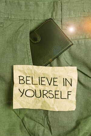 Word writing text Believe In Yourself. Business photo showcasing common piece of advice that you can do everything Small little wallet inside man trousers front pocket near notation paper Stock fotó