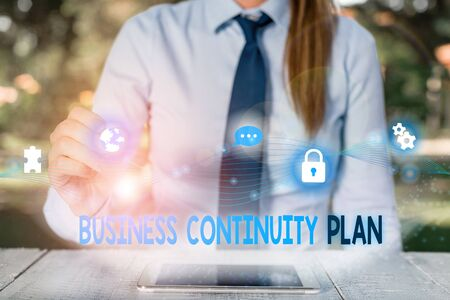 Conceptual hand writing showing Business Continuity Plan. Concept meaning creating systems prevention deal potential threats Female human wear formal work suit presenting smart device
