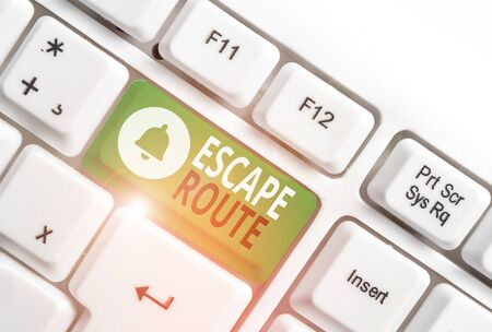 Conceptual hand writing showing Escape Route. Concept meaning a route by which a demonstrating may reach a place of safety White pc keyboard with note paper above the white background Foto de archivo