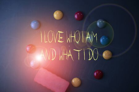 Word writing text I Love Who I Am And What I Do. Business photo showcasing High selfstem being comfortable with your job Round Flat shape stones with one eraser stick to old chalk black board Imagens