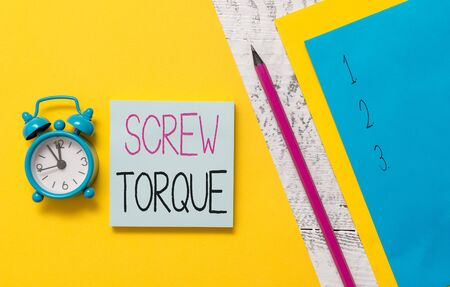Conceptual hand writing showing Screw Torque. Concept meaning measure of the twisting force required to spin the nut Notepads marker colored paper sheets alarm clock wooden background