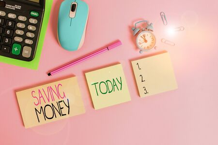 Conceptual hand writing showing Saving Money. Concept meaning putting money in an account in a bank o financial organization Notepads alarm clock calculator sheet marker colored background Archivio Fotografico