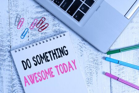 Handwriting text Do Something Awesome Today. Conceptual photo Make an incredible action motivate yourself Slim metallic laptop blank spiral notepad pens clips lying wooden table