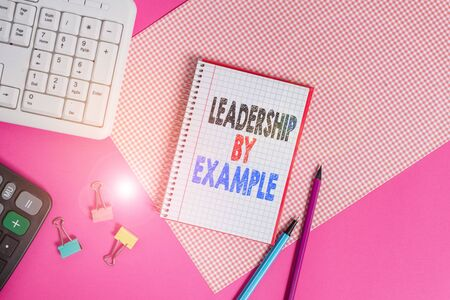Text sign showing Leadership By Example. Business photo showcasing Becoming role model for showing Have great qualities Writing equipments and computer stuffs placed above colored plain table