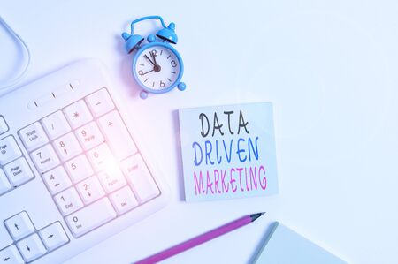 Conceptual hand writing showing Data Driven Marketing. Concept meaning Strategy built on Insights Analysis from interactions Keyboard with empty note paper and pencil white background Stock Photo
