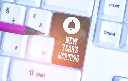 Conceptual hand writing showing New Year S Resolutions. Concept meaning Wishlist List of things to accomplish or improve White pc keyboard with note paper above the white background