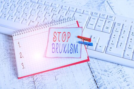 Conceptual hand writing showing Stop Bruxism. Concept meaning put an end to a condition which you grind or clench the teeth notebook reminder clothespin with pinned sheet light wooden Standard-Bild
