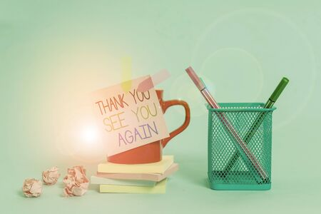 Word writing text Thank You See You Again. Business photo showcasing Appreciation Gratitude Thanks I will be back soon Cup pens holder note banners stacked pads paper balls pastel background