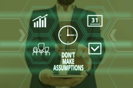 Text sign showing Don T Make Assumptions. Business photo showcasing putting plan in future with percentage happening Male human wear formal work suit presenting presentation using smart device Stock Photo