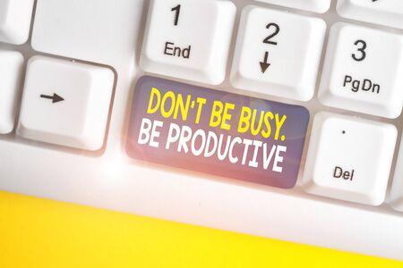 Escritura a mano conceptual que muestra que no esté ocupado, sea productivo. Concepto Significado trabajar eficientemente Organice su horario de tiempo Teclado de pc blanco con papel de nota sobre el fondo blanco.