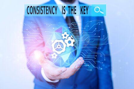 Escritura de texto Word la consistencia es la clave. Foto de negocios mostrando dedicación total a una tarea, un proceso de formación de hábito, ropa humana masculina, traje de trabajo formal que presenta la presentación mediante un dispositivo inteligente