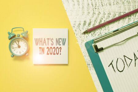 Writing note showing What S New In 2020 Question. Business concept for Expectation and Surprises for the coming Year Notepad clipboard colored paper sheet alarm clock wooden background
