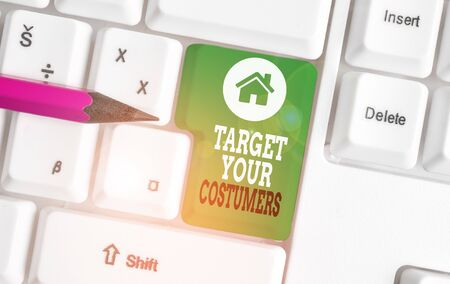 Text sign showing Target Your Costumers. Business photo showcasing Specific Range and Interest Potential Users and Buyers White pc keyboard with empty note paper above white background key copy space