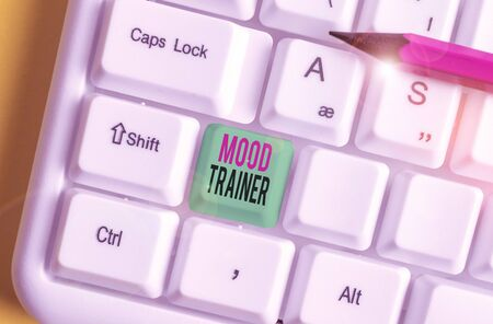 Text sign showing Mood Trainer. Business photo showcasing a demonstrating who trains to alleviate mood disorders of a demonstrating White pc keyboard with empty note paper above white background key copy space
