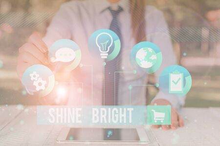 Writing note showing Shine Bright. Business concept for make an effort to live normally when in a difficult situation Female human wear formal work suit presenting smart device 스톡 콘텐츠