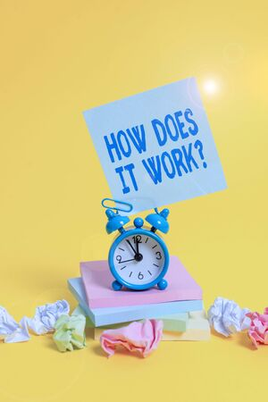 Text sign showing How Does It Work Question. Business photo showcasing Asking on how stuff being build or operates Alarm clock sticky note paper balls stacked notepads colored background Banco de Imagens