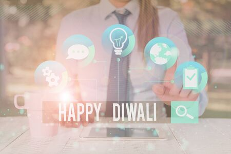 Handwriting text writing Happy Diwali. Conceptual photo festival of lights that celebrated by millions of Hindus Female human wear formal work suit presenting presentation use smart device Stock Photo