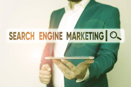 Text sign showing Search Engine Marketing. Business photo showcasing promote Website visibility on searched result pages Man in the blue suite and white shirt holds mobile phone in the hand Stock Photo