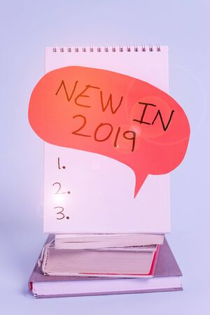 Writing note showing New In 2019. Business concept for what will be expecting or new creation for the year 2019 Spiral notebook speech bubble stacked old books cool pastel background