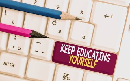 Conceptual hand writing showing Keep Educating Yourself. Concept meaning dont stop studying Improve yourself using Courses White pc keyboard with note paper above the white background Stock Photo