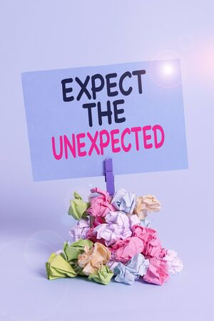 Text sign showing Expect The Unexpected. Business photo text Anything can Happen Consider all Possible Events Reminder pile colored crumpled paper clothespin reminder blue background