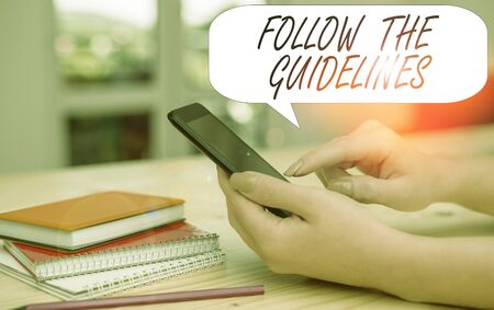 Conceptual hand writing showing Follow The Guidelines. Concept meaning Manual of Style Follow a Specified Rule Accordingly woman using smartphone and technological devices inside the home Stok Fotoğraf