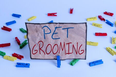 Word writing text Pet Grooming. Business photo showcasing hygienic care and enhancing the appearance of the pets Colored clothespin papers empty reminder white floor background office Imagens
