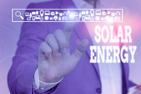 Handwriting text Solar Energy. Conceptual photo radiation from the Sun capable of producing heat or electricity Male human wear formal work suit presenting presentation using smart device